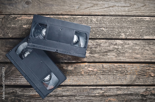Fotografering  Two plastic video cassettes from the 80s on a rustic wooden table