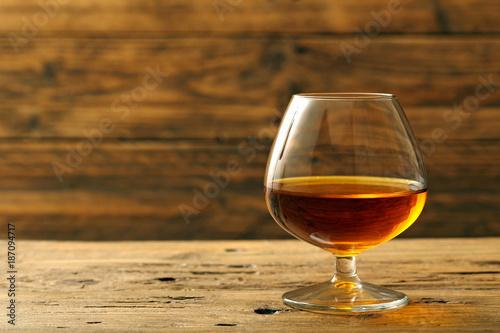 cognac o brandy bicchiere con bevanda alcolica su sfondo legno rustico Wallpaper Mural