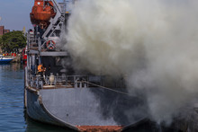 Fire On A Ship. The Crew Quenched The Fire During The Military Scientists At The Port. Disaster On A Vessel And Struggle For Life.
