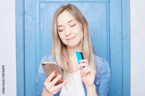 Fototapeta Horizontal portrait of blond female has dreamful expression, imagines new clothes, going do online shopping, holds modern cell phone and plastic card, isolated over white background with copy space. obraz