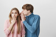 Handsome young fair-haired male student in blue sweater, whispering something into ear of stylish blonde girl, sharing gossips and secrets. Cute female looking in shock and surprise at camera.