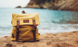 Hipster hiker tourist yellow backpack closeup on background blue sea sunset ocean horizon, blurred panoramic seascape sunrise blank mockup, traveler relax holiday concept, sunlight in trip vacation