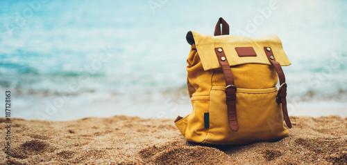 Foto  Hipster hiker tourist yellow backpack closeup on background blue sea enjoying su