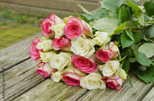 Photo pink and white roses on the wooden table