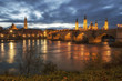 The Cathedral-Basilica of Our Lady of the Pillar and Stone bridge at the night in Zaragoza on the Ebro River, Spain.