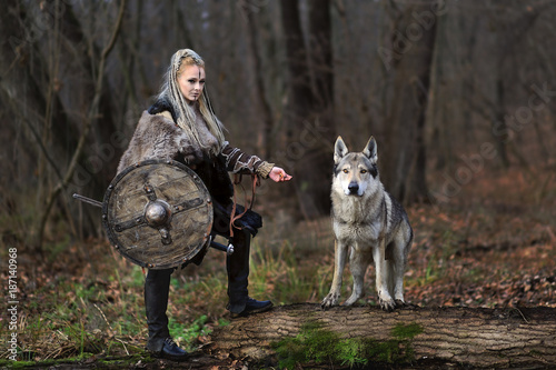 Photo Beautiful viking warrior woman in traditional warrior clothes, with ax and shiel