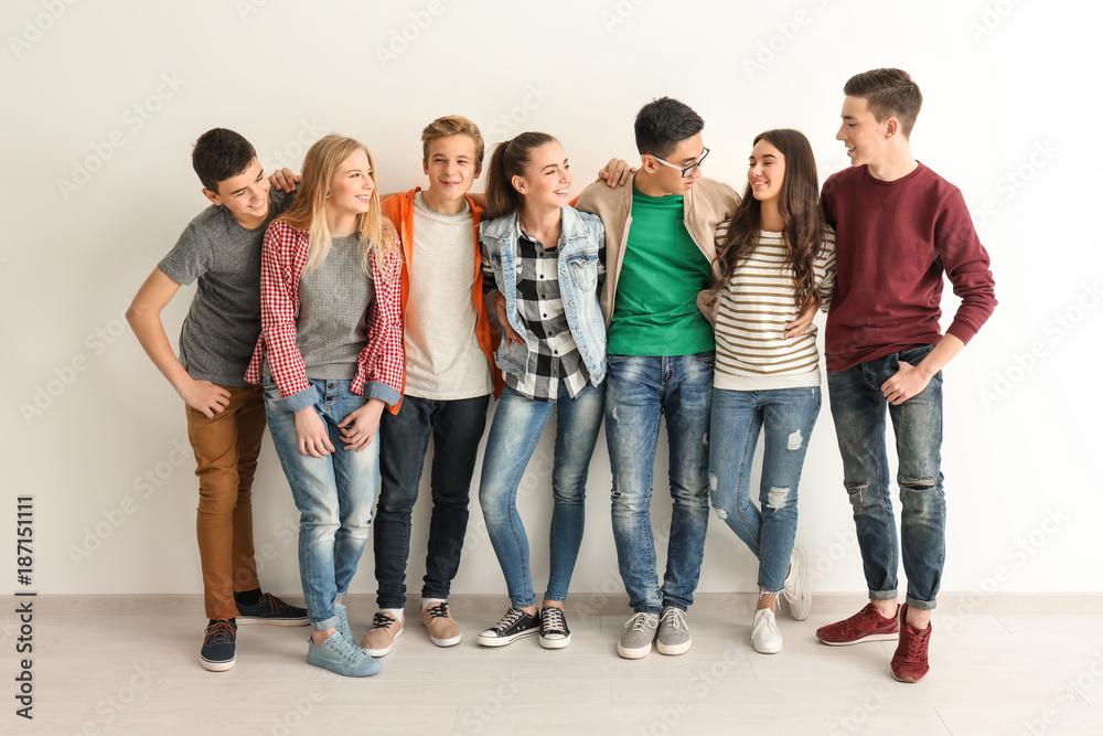 Fototapety, obrazy: Group of cute teenagers near white wall