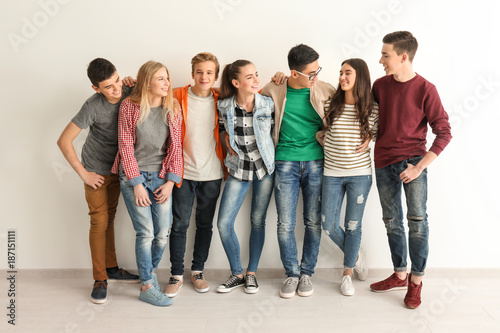 Group of cute teenagers near white wall Fototapet