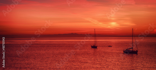 Beautiful colorful sunset at the sea with two sailing boats . Beauty world natural outdoors travel background