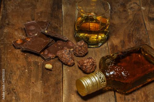 Fototapeta A glass of cognac or whiskey on a rustic table with chocolate and truffles. obraz na płótnie