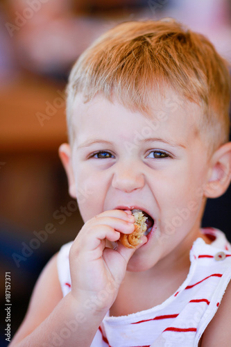 Photographie Portrait of blonde caucasian child eating a piece of bread