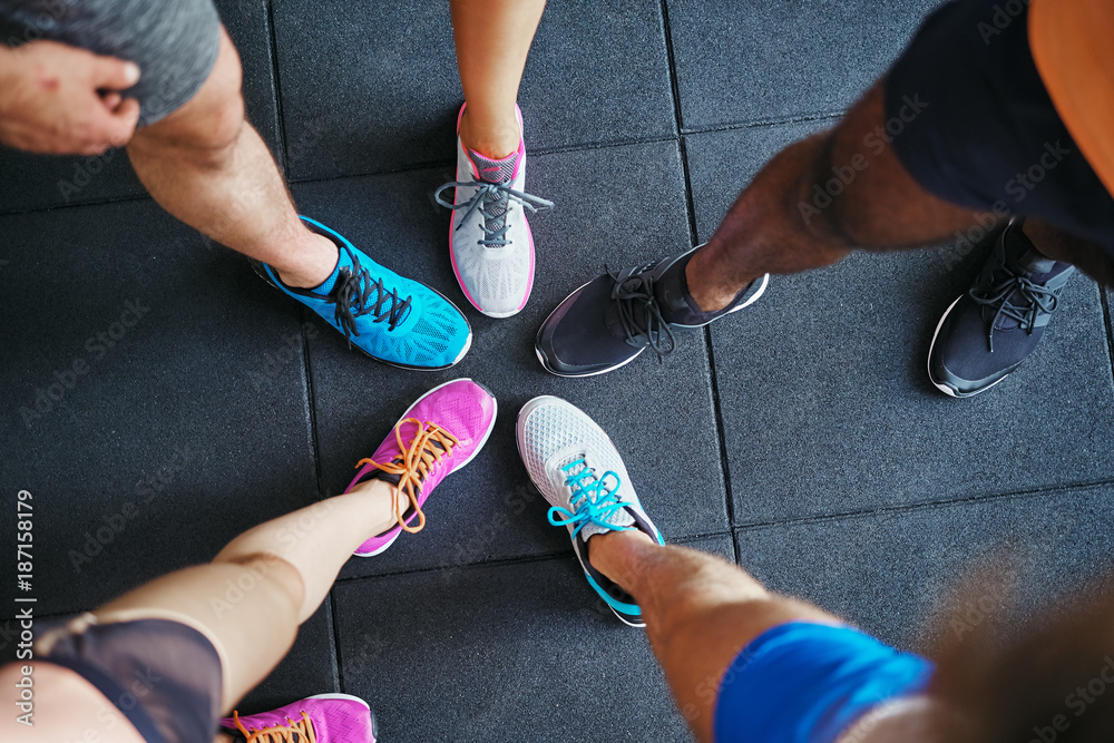 Fototapeta Diverse people wearing running shoes standing in a gym