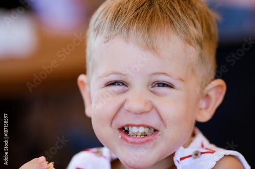 Portrait of blonde caucasian child eating a piece of bread Tableau sur Toile