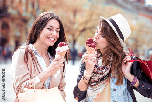 Two beautiful girls eating ice cream and shopping. Poster