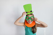 The lovely girl in a mask of a leprechaun for a St. Patrick's Day