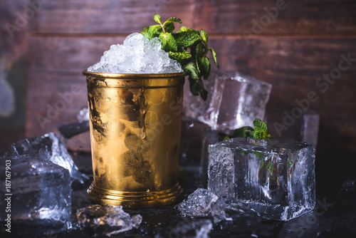 A container with ice stands among ice cubes and mint. Canvas-taulu
