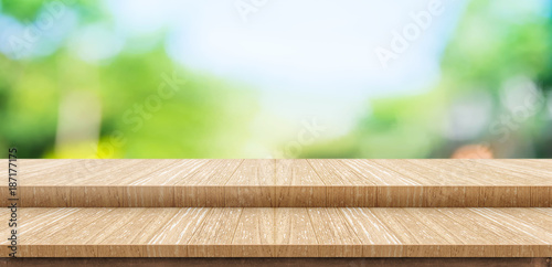 Poster Roe Empty step wood table top food stand with blur green park tree background bokeh light,Mock up for display or montage of product,Banner for advertise on online media,nature business presentation