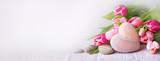 Fototapeta Tulipany - Beautiful tulips with stone heart on light wooden background