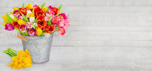 Frühling - Tulpen und Narzissen mit Eimer und Dekoration auf Holz