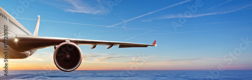 Detail of wing of commercial airplane jetliner flying above clouds in beautiful sunset light.