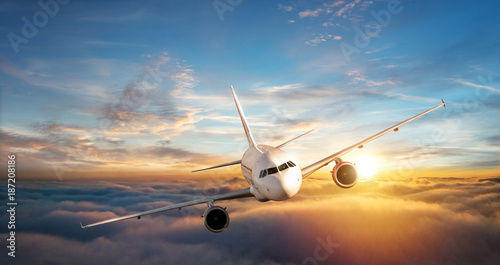 Commercial airplane jetliner flying above clouds in beautiful sunset light.