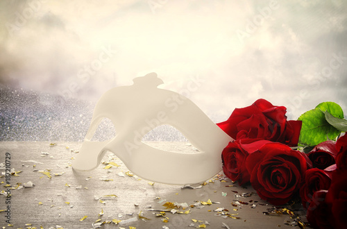 Image of elegant venetian mask on red silk and glitter shiny background.