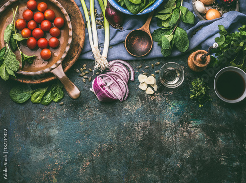Fototapeta Vegetarian cooking ingredients with fresh seasoning on rustic kitchen table with spoon , top view, place for text.  Clean, vegan food and healthy eating. obraz