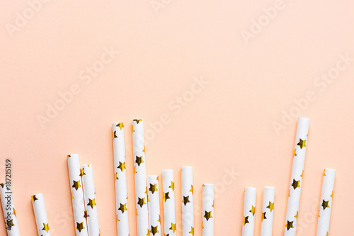 Elegant White Paper Drinking Straws with Golden Stars Pattern Scattered as Border Frame on Pink Peachy Background Poster