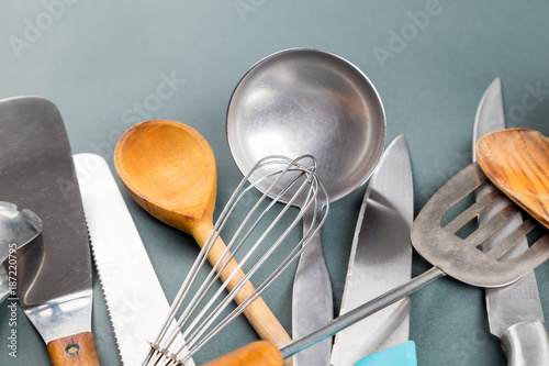 Fotografía  Used home kitchenware with scratches on gray paper background