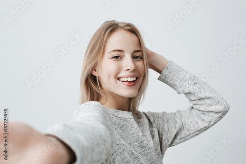 Fotografía Attractive dark-eyed blonde female dressed casually having delightful look smiling broadly