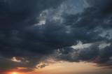 Tło. Burzwe ciemne chmury na tle zachodzącego słońca