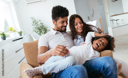 Obraz Family lifestyle portrait of a mum and dad with their kid - fototapety do salonu