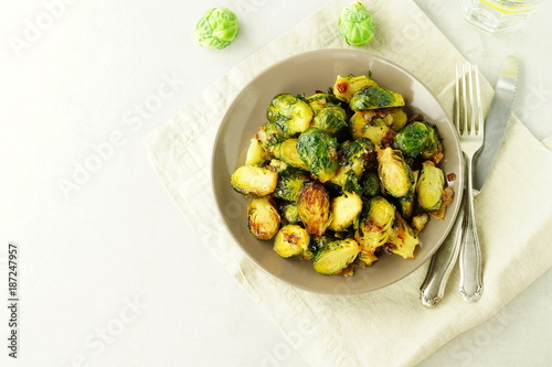 Photo sur Toile Bruxelles Homemade Roasted Brussel Sprouts with salt, pepper and onions in a beige plate on grey background. top view. copy space