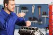 Mechanic repairing a motorbike engine in a workshop
