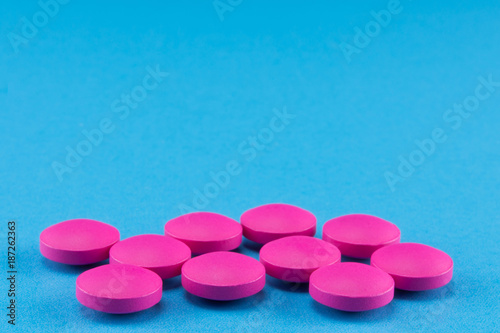 close up of pink round pills on blue background Tableau sur Toile