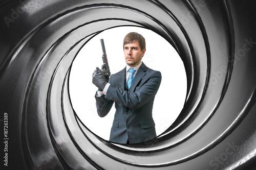Fotografie, Obraz  View through gun barrel on agent with pistol.