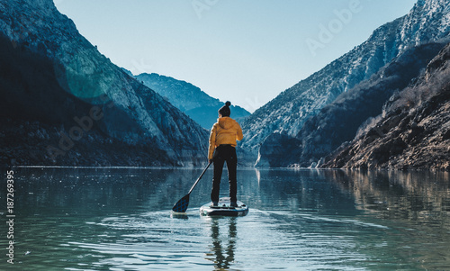 a woman with yellow plumber paddle surfing on a lake in a snowy mountain landsca Wallpaper Mural