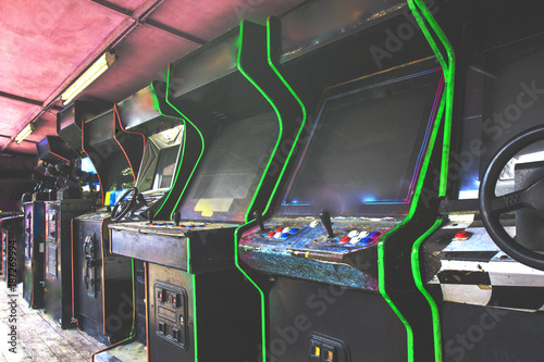 Photo Old used classic forgotten Vintage Arcade in room and none of players playing video games in the frame