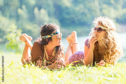 Fotografía Pretty free hippie girls laying on the grass - Vintage effect photo