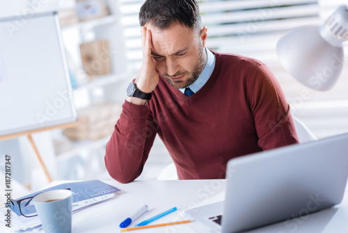 Feeling dizzy  Tired young unhappy man sitting at the table in his