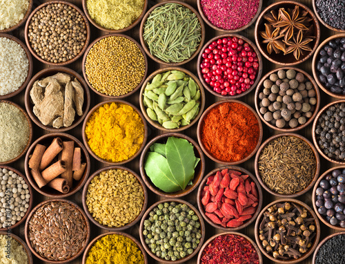 Spoed Fotobehang Aromatische Spices and herbs background. Condiments on the table spread out by a rainbow