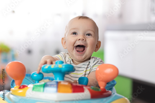Portrait of baby in baby walker. Expressive child plays toys.