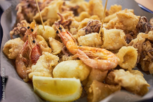 Staande foto Schaaldieren A typical Italian dish fried seafood: shrimp, squid, octopus and a slice of lemon. Italian fast food. Fish and chips
