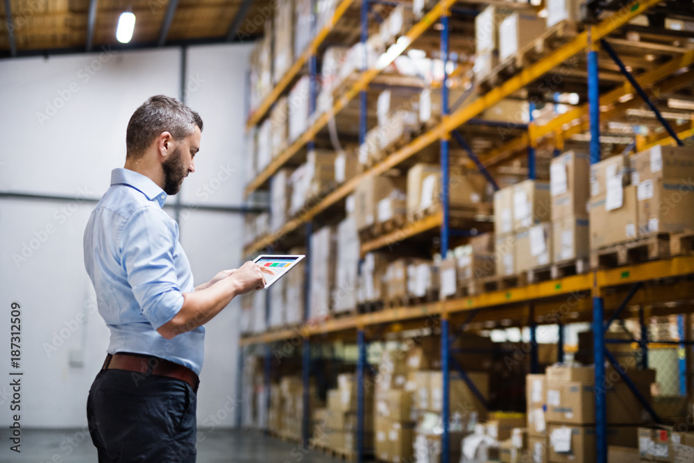 Fototapeta Man warehouse worker with a tablet.