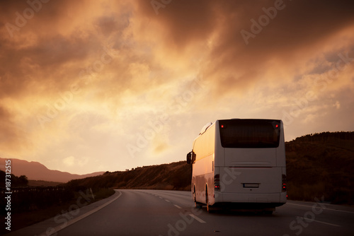 Canvastavla White bus driving on road towards the setting sun