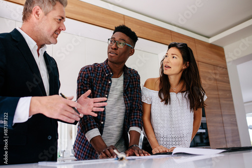 Photo  Interracial couple having consultation with a realtor
