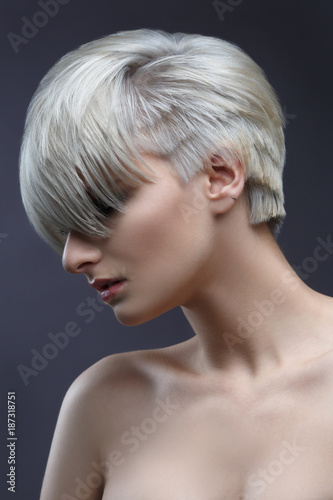 Photo  Fashion beauty portrait of a blonde girl with a stylish short haircut, bangs closes her eyes