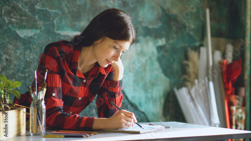 Portrait young woman artist painting scetch on paper notebook with pencil