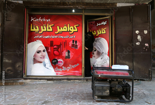 A Palestinian Woman Looks Out Of A Hairstyle Salon As A Generator Is