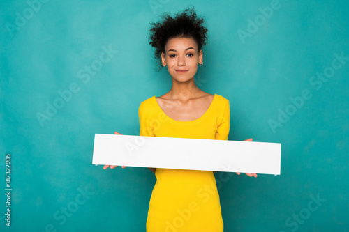 Fotografering  Young african-american woman holding blank banner